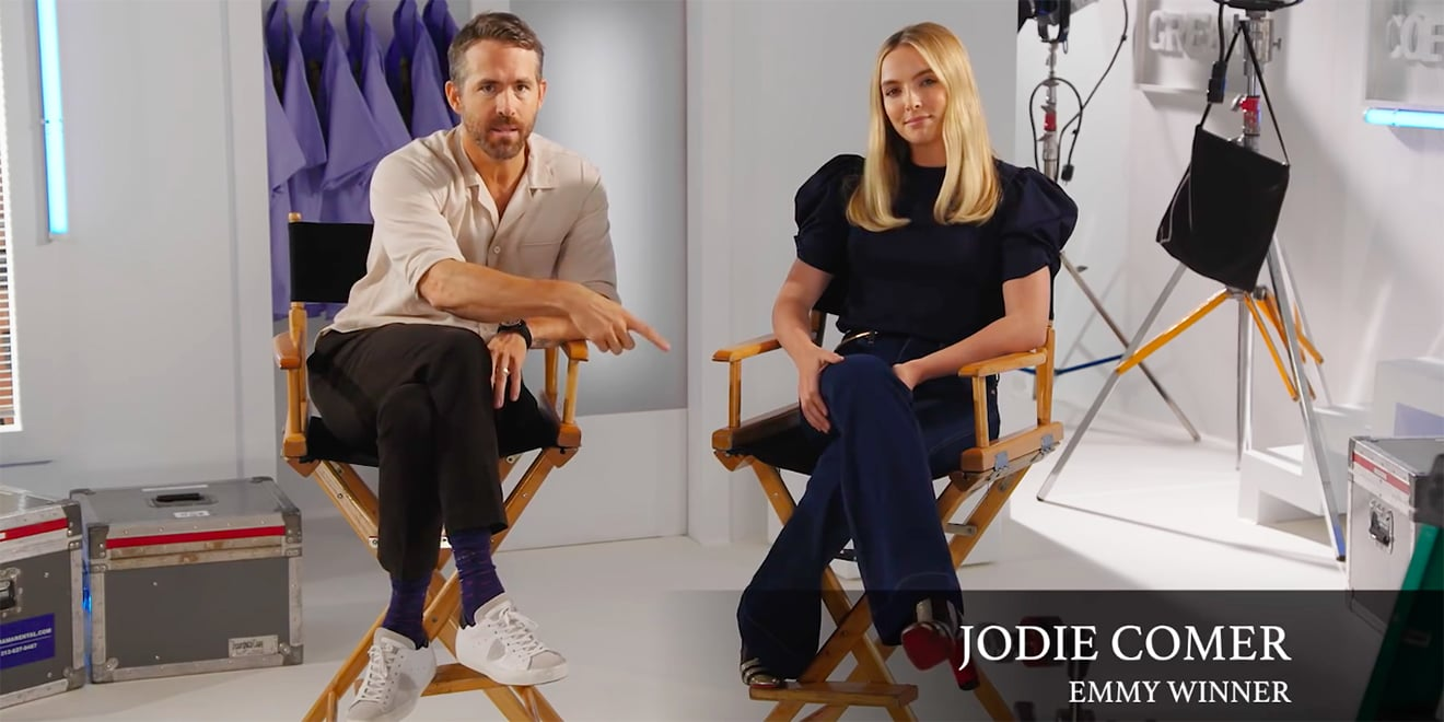 Ryan Reynolds sitting in a chair next to Jodie Comer