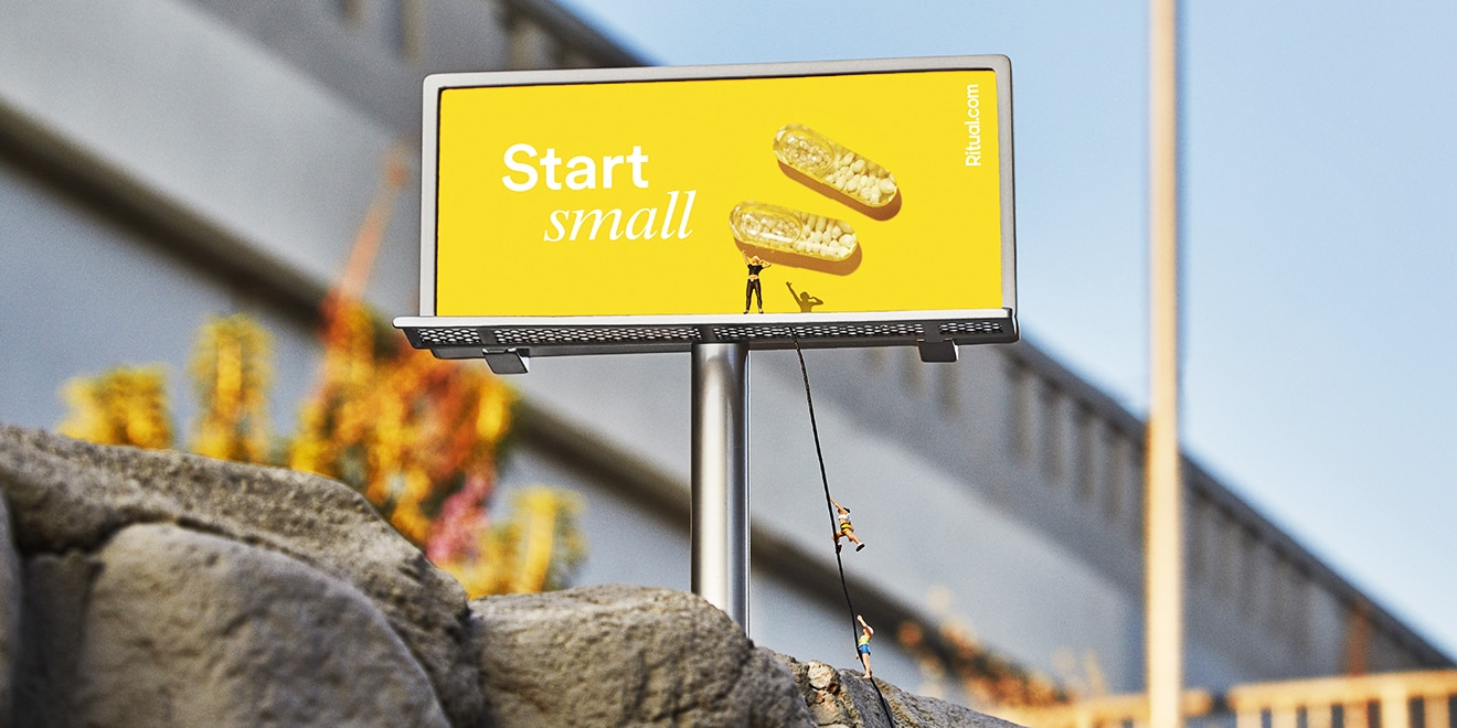 "A shot of a Ritual billboard that says ""Start small"" with one person standing on it and two other people trying to climb up"