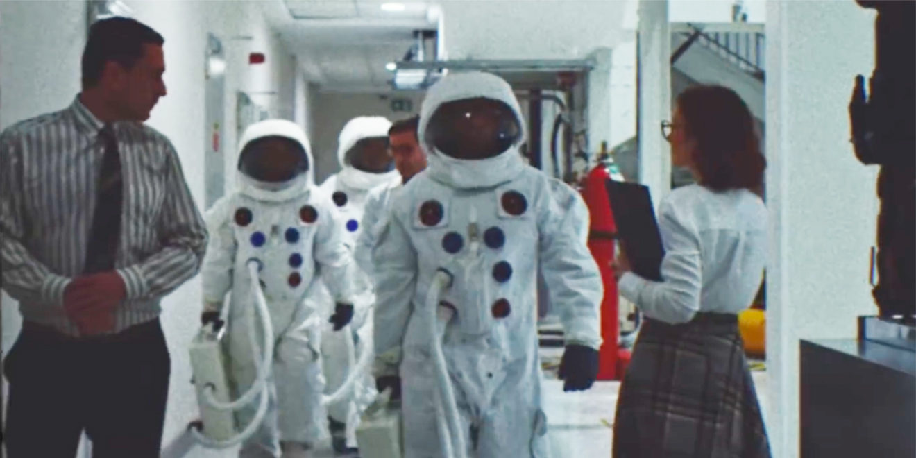 Astronauts walk toward the camera in footage that seems to date from the 1960s