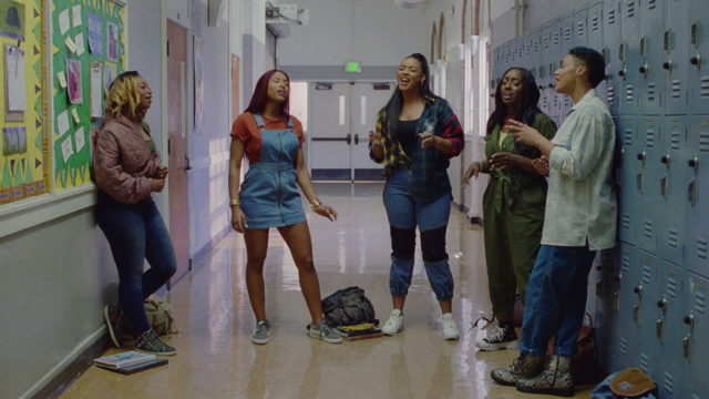 A still of students singing in a school hallway