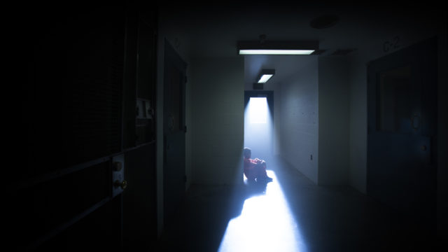 a child sitting in a dark hallway