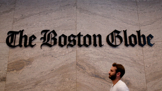 A man in front of The Boston Globe logo
