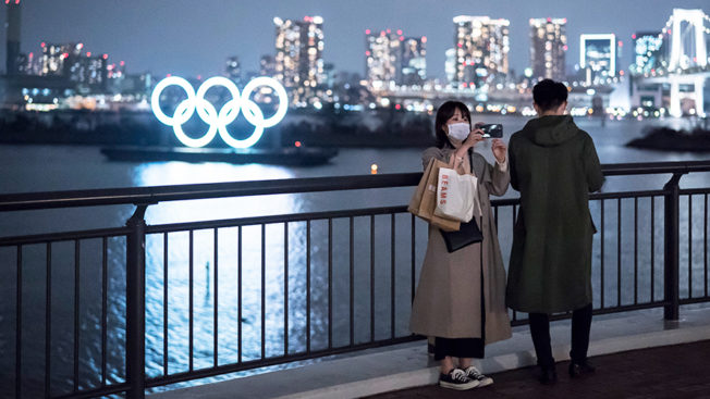 Woman wearing mask taking photos in front of city skyline