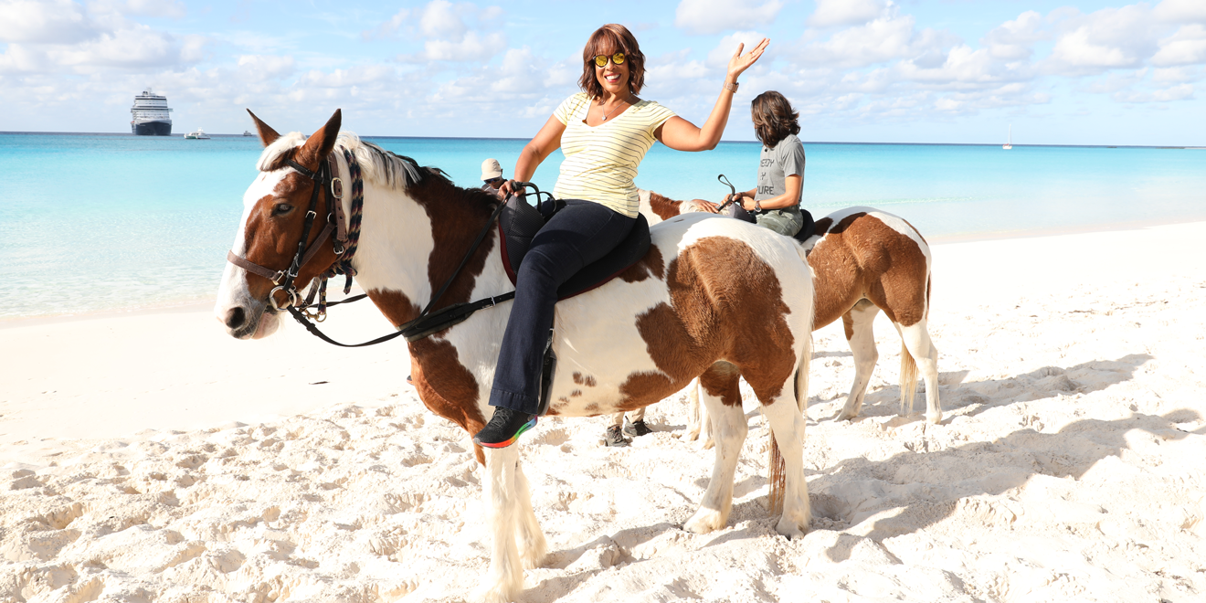 gayle king on a horse on the beach