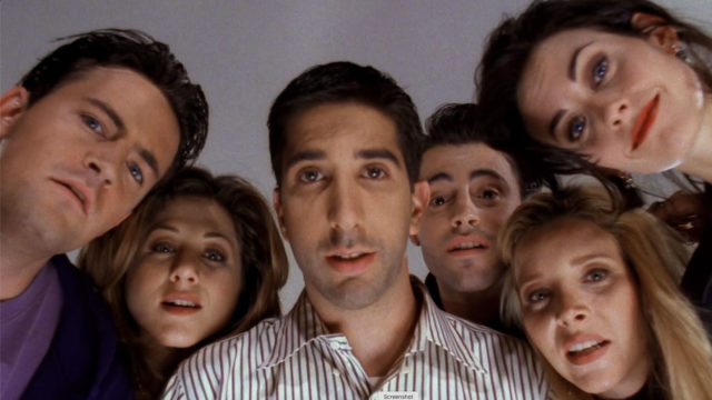 the cast of friends looking into a camera lens