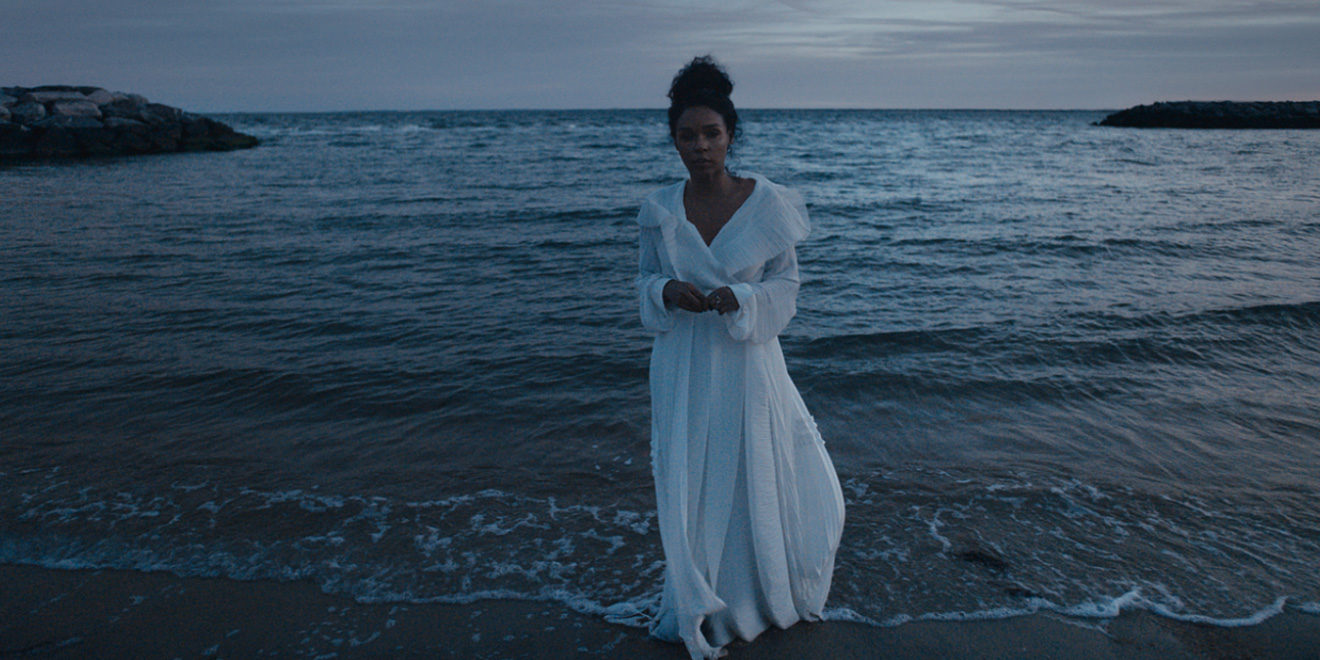 janelle monae standing on a beach in a white dress