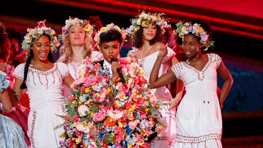 janelle monae holding a ton of flowers surrounded by women of color dressed in white with flower crowns