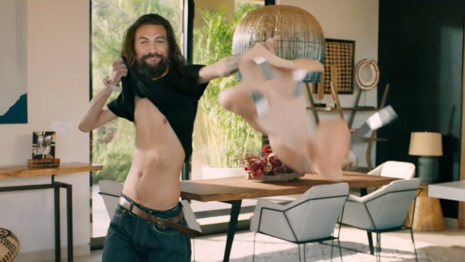 Jason Momoa lifting his shirt to show a skinnier body holding a muscle suit next to it