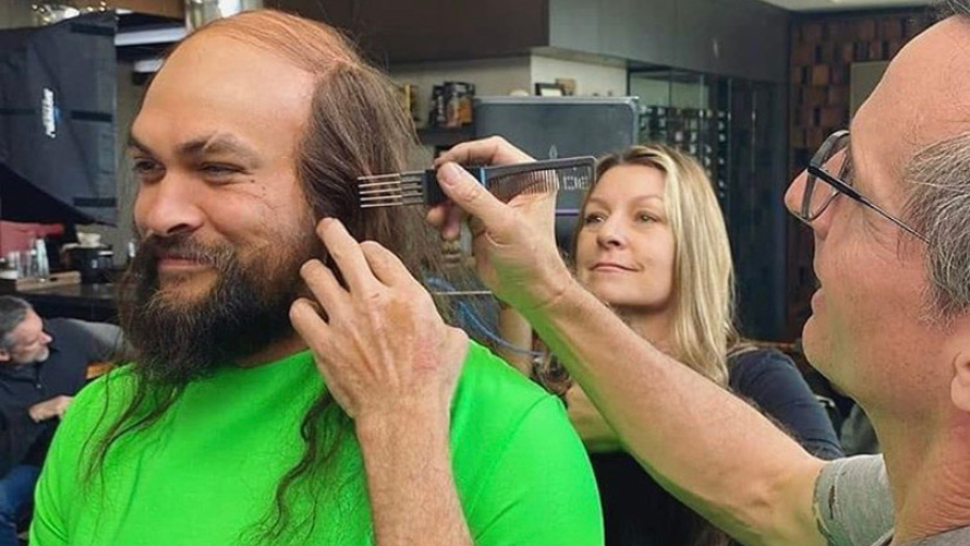 jason momoa in a lime green shirt getting his wig fitted