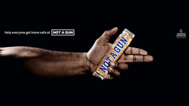an arm and hand holding a candy bar
