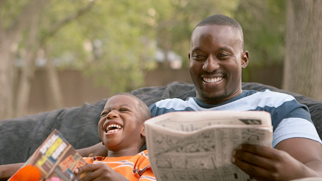 A man reading a newspaper and a boy reading a book