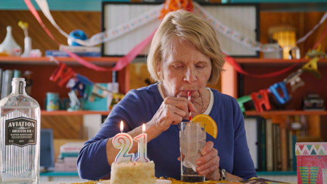 Arlene Manko drinking an alcoholic beverage next to a birthday cake with 2 and 1 candles and a bottle of Aviation Gin