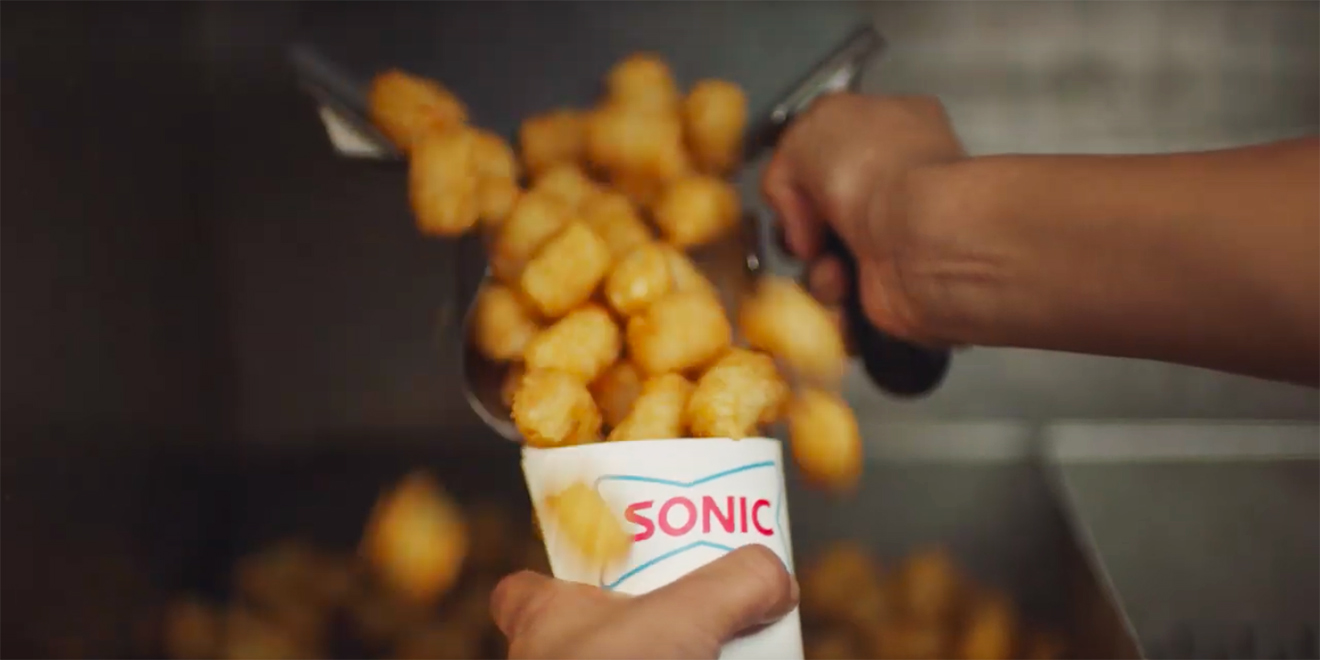 A hand holding Sonic tater tots pushing the tater tots on to a tray