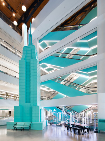 a turquoise skyscraper inside a lobby