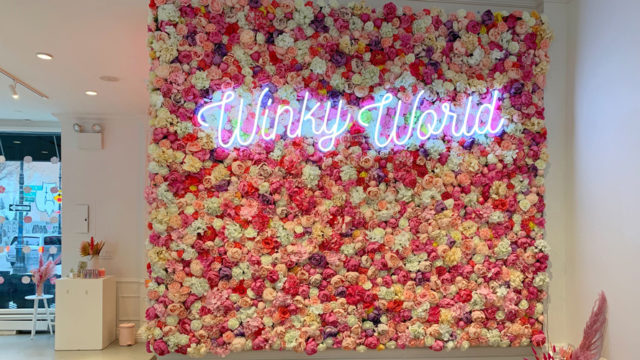 A wall of flowers with a neon sign that says Winky World