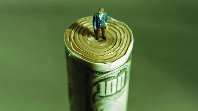 a tiny man standing on a giant roll of $100 bills
