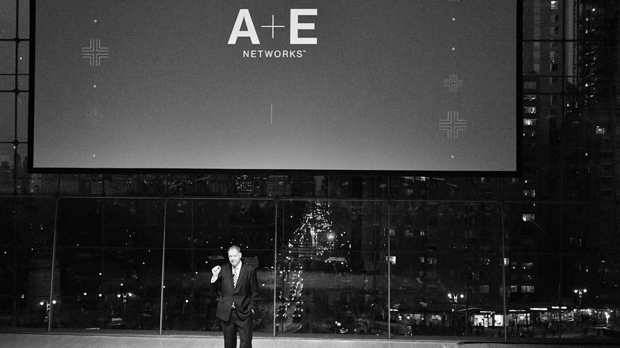 a man onstage at A+E's 2019 Upfront