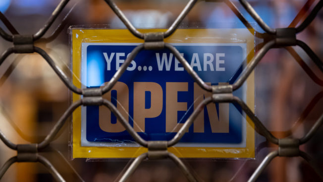 Open for business sign behind chain-link fence