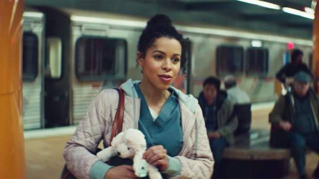 A woman at a train station wearing scrubs and holding a stuffed animal in her purse