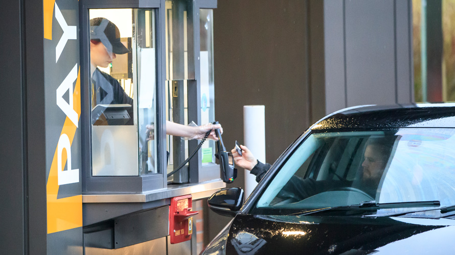 a fast food worker handing over food at a drive through window