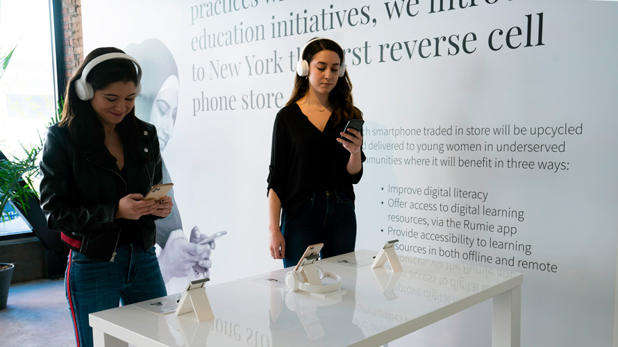"""Two women stand with phones in hand at ecoATM and Rumie's new """"reverse cell phone store"""" in New York"""