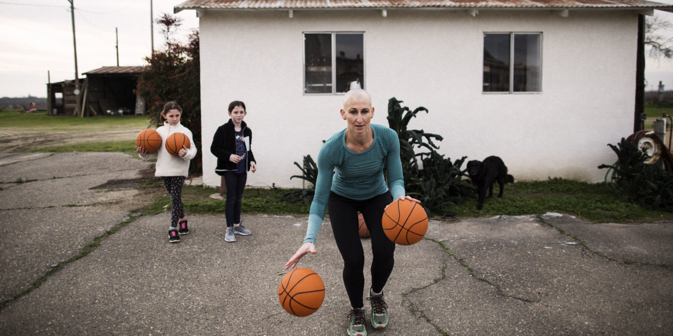 An older woman with a bald head plays basketball with two children