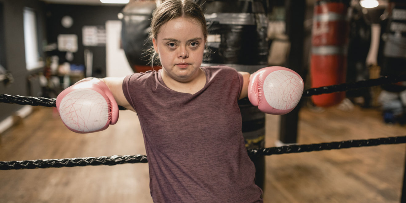 A young woman with Down Syndrome wearing boxing gloves leans against the ropes of a boxing ring