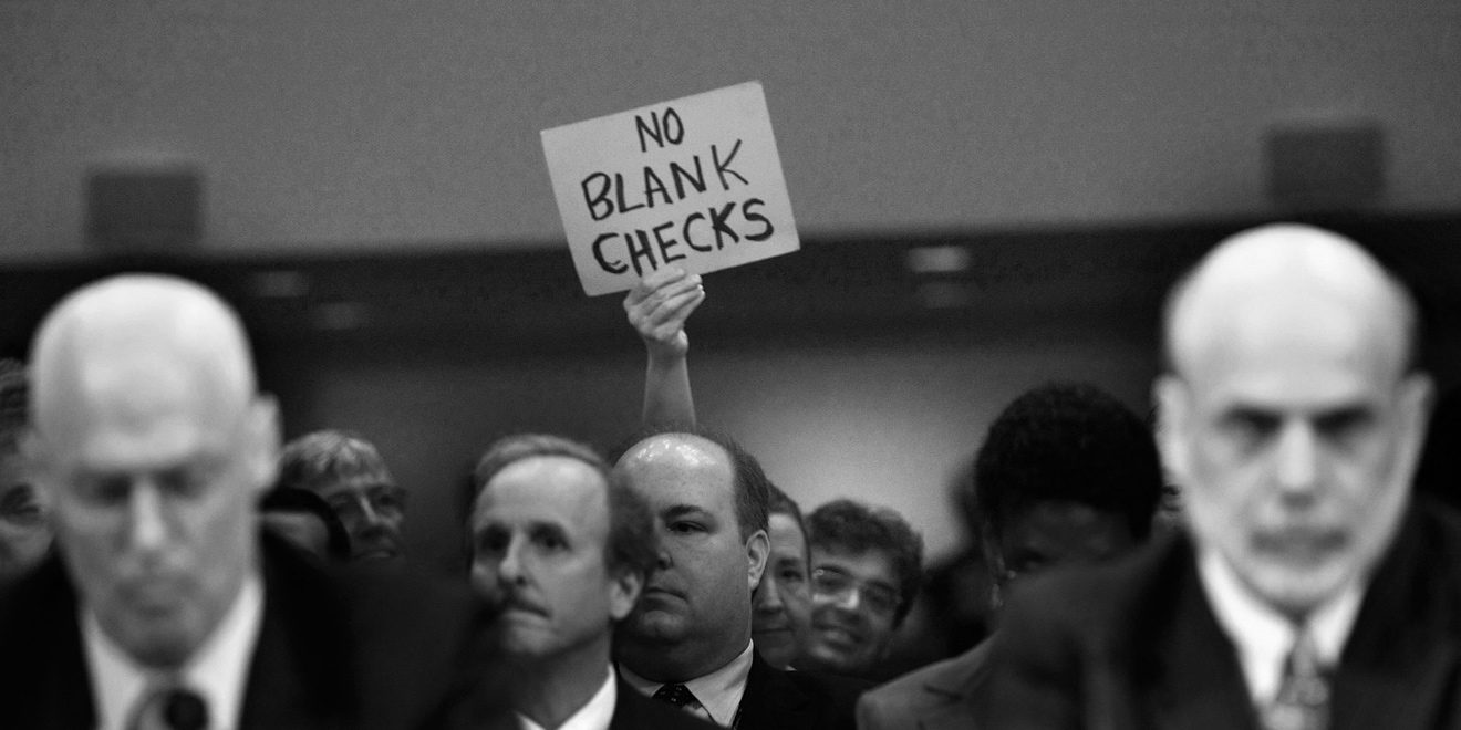 """Man in crowd holding up sign that says """"No blank checks"""""""