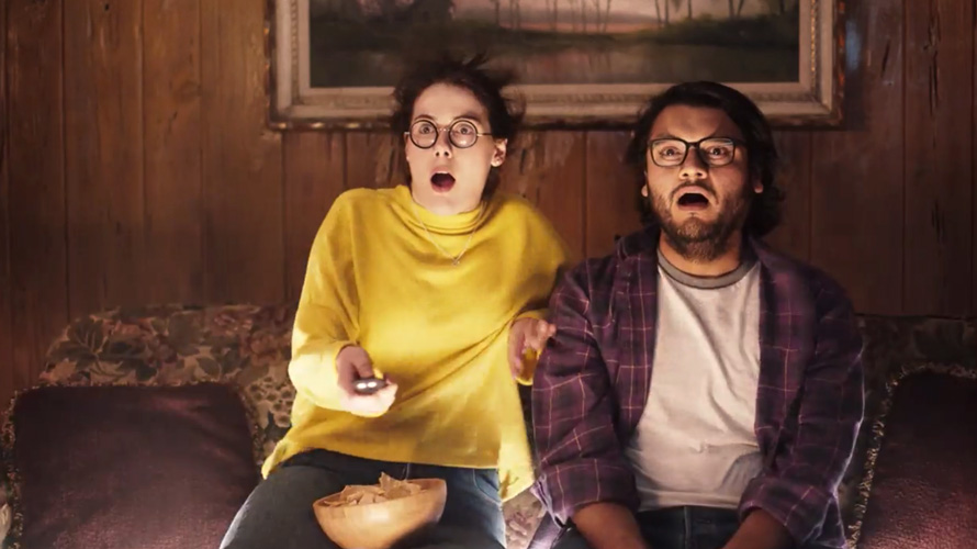 A woman with a shocked face holding a remote with chips in her lap watching TV next to a man with a shocked face