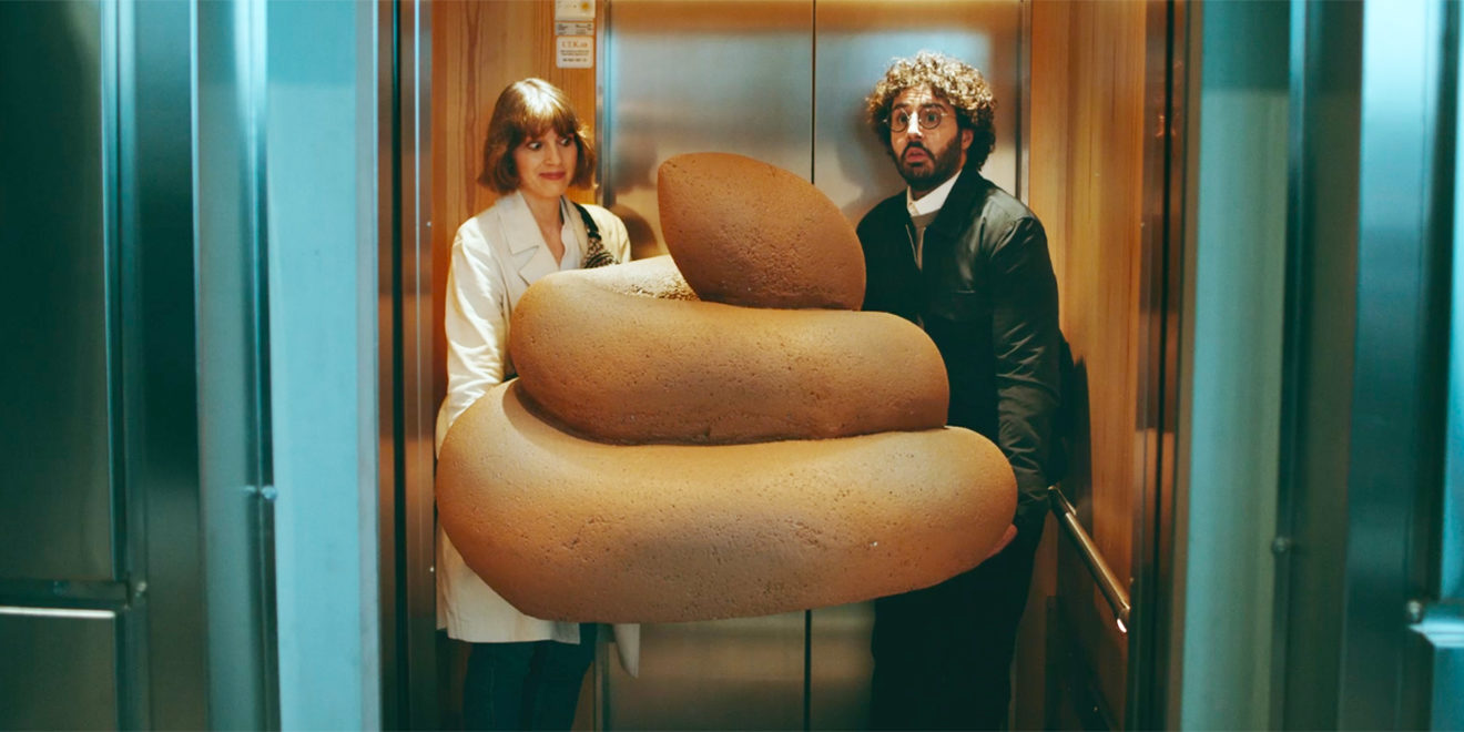 Two coworkers hold a giant poop statue in an elevator