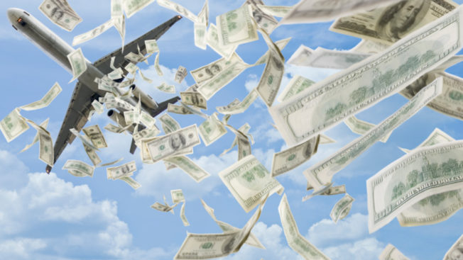 an airplane flying through a blue sky with dollar bills falling from it