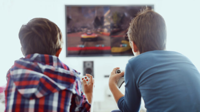 Two kids playing a video game in front of a TV screen