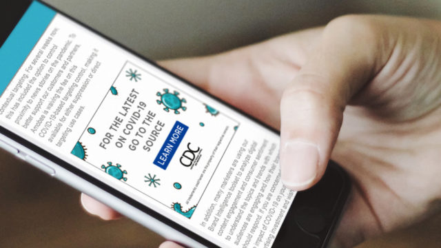 A person's hand holding a smartphone that has an ad from the CDC
