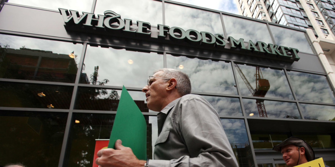 a striking worker stands outside Whole Foods with a green sign