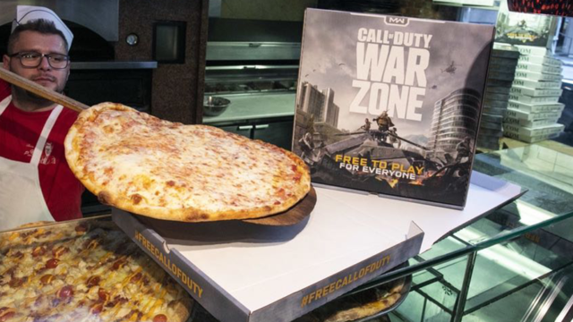 A pizza pie being put into a box next to a Call of Duty sign