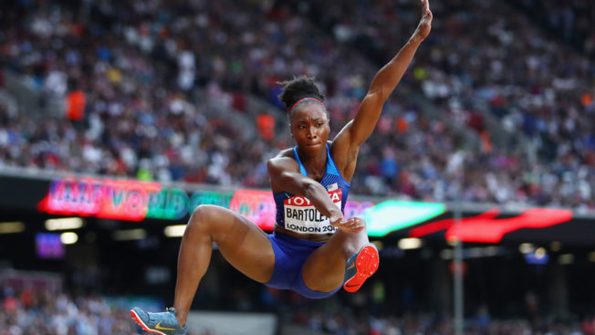 Track and field athlete Tianna Bartoletta mid-jump in the air during a competition in a crowded stadium