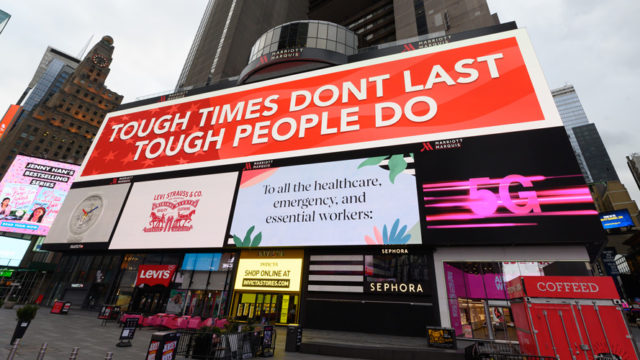 Photo of big billboard ads with one on top that says, 'Tough Times Don't Last Tough People Do'
