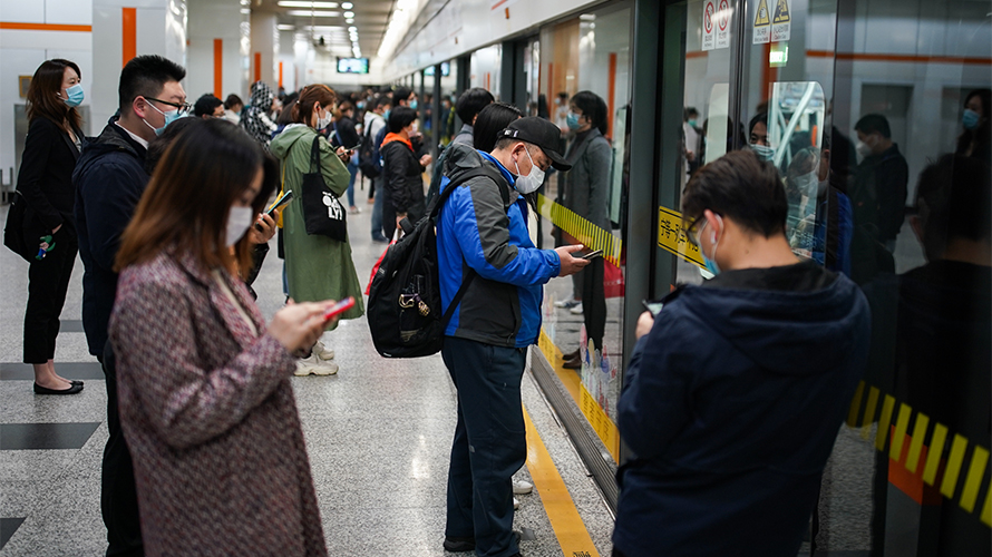 people standing on a subway platform with masks on using their phones