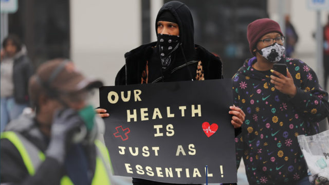 Chris Smalls holding a sign that says, 'Our health is just as essential'