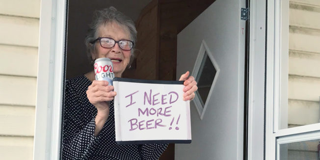 Woman holding a Coors Light and a sign that says, 'I need more beer'
