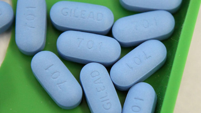 A handful of blue Truvada pills stamped with the Gilead manufacturing logo