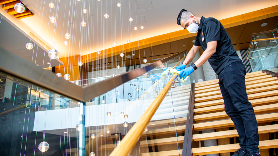 a hotel worker wiping down a stair handrail