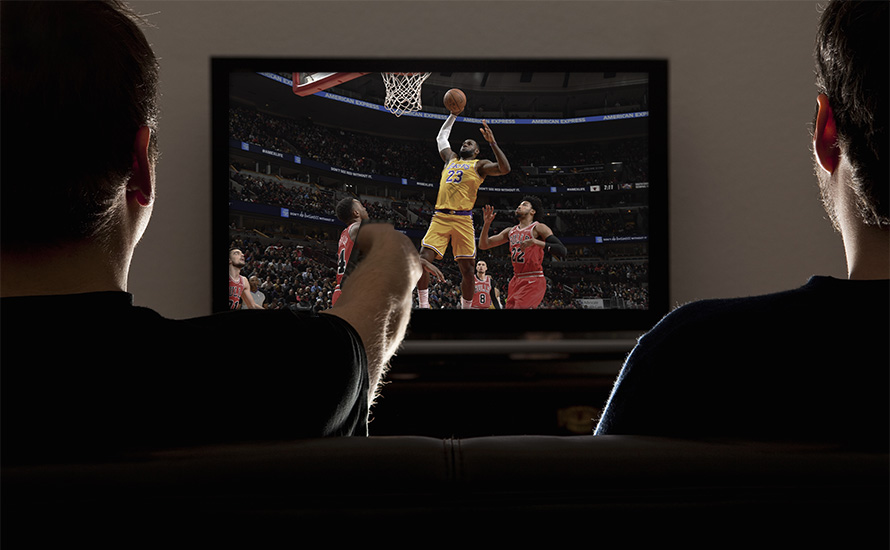 People watch Lakers basketball on a TV.