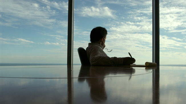 A person sitting at a big table looking out of a window