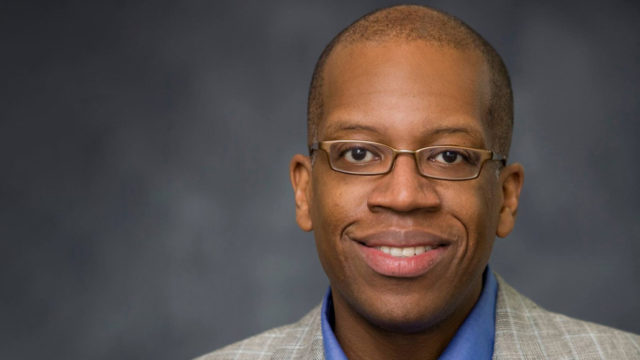 a headshot of a black man with glasses in a tan suit jacket