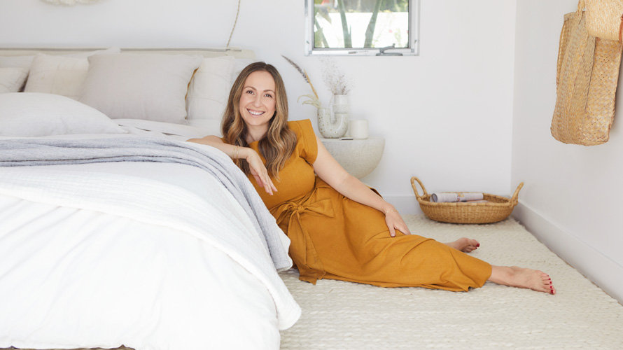 Ariel Kaye, CEO of Parachute, leaning on a bed
