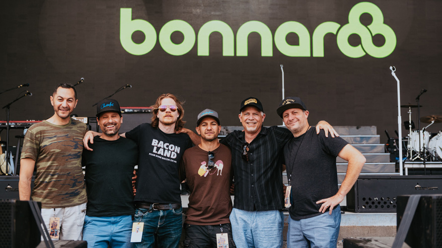 five men standing in front of a sign that says Bonnnaroo