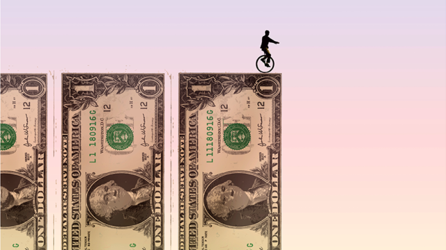 Three $1 bills and the shadow of a person on a unicycle on top of one bill