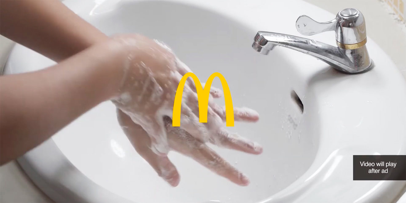 A photo of a person washing their hands in a sink with the McDonald's logo