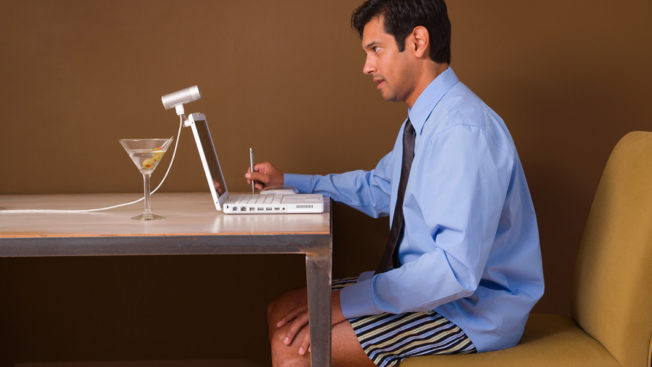 a man sitting at a desk in his underpants with a button-down shirt on and a martini next to his laptop